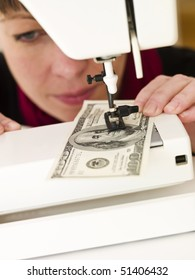 Woman holding with Hundred dollar bank note in a sewing machine