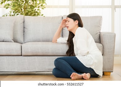 woman holding hurting tummy suffering stomach cramp and period pain sitting on floor. lifestyle and health concept. mixed race asian chinese model.