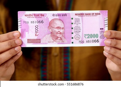 Woman holding Indian 2000 rupee notes against white background