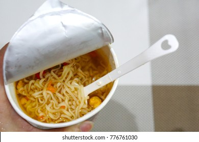 Woman holding the Instant noodles cup with plastic fork. Copy space. Quick and simple food. Slow life.