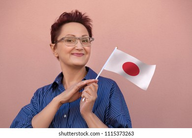 Woman holding Japan flag. Nice portrait of middle aged lady 40 50 years old with a national Japanese flag over pink wall background.Learning Japanese language. Visit Japan concept.