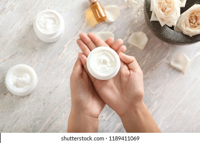 Woman holding jar with body cream over light table