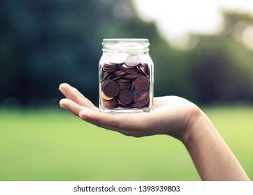 Woman holding jar of coins. Saving Money concept.