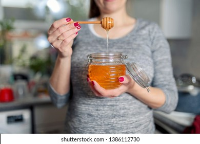 Woman holding jar of honey in kitchen