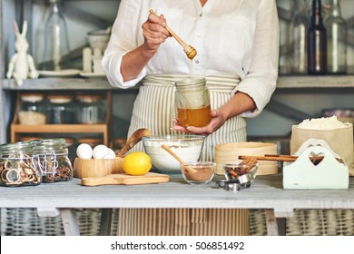 Woman holding jar of honey preparing dough for  baking gingerbread in the kitchen.