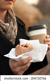 A Woman Holding a Jelly Donut and a Coffee on a Fall Day.