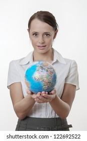 woman holding up a jigsaw globe puzzle