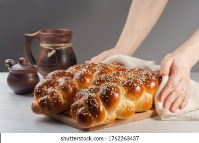 Woman holding just made Challah bread with white cover, Jewish cuisine.  Decorated with sesame and poppy seeds.
