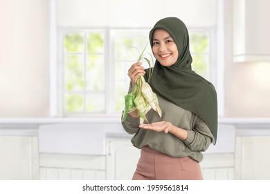 woman holding ketupat on white background