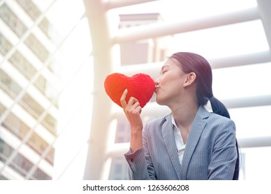 Woman is holding and kissing heart shape