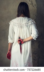 Woman holding knife back on her hand with blood, halloween concept