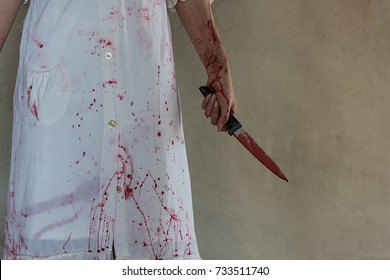 Woman holding knife with blood, halloween concept