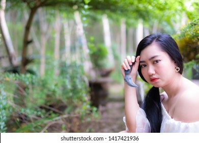 Woman holding knife karambit in hand on a blurred background