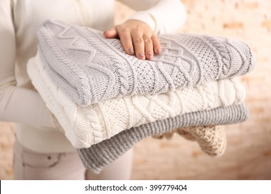 Woman holding knitted clothes, closeup