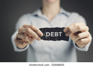 Woman holding a label with the word debt toward the camera.