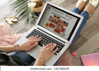 Woman holding laptop with open fashion blogger site on floor, closeup