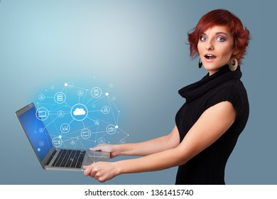 Woman holding laptop projecting cloud based system symbols and informations