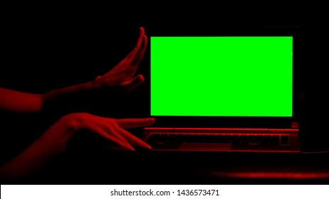 Woman holding laptop, red illumination, concept of adult sites, escort services