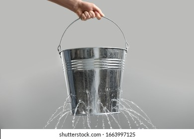 Woman holding leaky bucket with water on light grey background, closeup