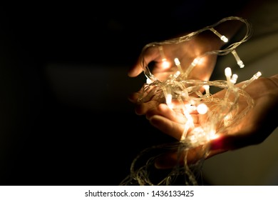 Woman holding lights in her hands, Give a Gift. Romantic Hipster Concept. banner space for adding text