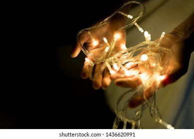 Woman holding lights in her hands, Give a Gift. Romantic Hipster Concept.