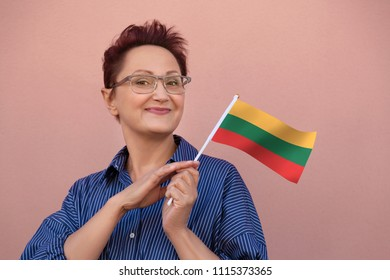 Woman holding Lithuania flag. Nice portrait of middle aged lady 40 50 years old with a national Lithuanian over pink wall background.Learning Lithuanian language. Visit Lithuania concept.