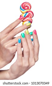 Woman is holding lollipop candy. Female fingers with bright green, yellow, pink and blue nails manicure. Girl's hands isolated on white background
