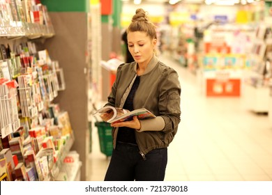 Woman holding magazine,buying a book in a store