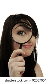 woman holding a magnifying glass up to her eye so it looks really big