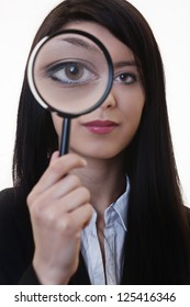 woman holding a magnifying glass over her eye