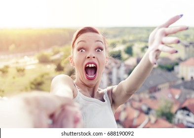 woman holding male hand and screaming above the big city, excited girl feeling adrenaline on the top of building, copy space