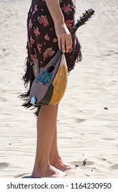 woman holding a mandolin at the beach