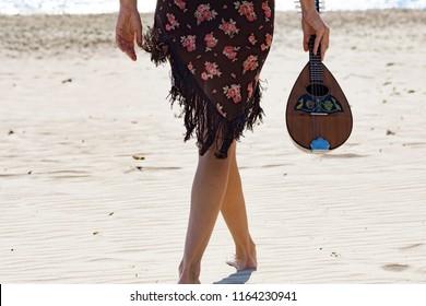 woman holding a mandolin while walking at the beach