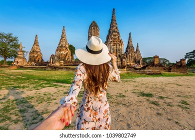 Woman holding man's hand and leading him to Ayutthaya Historical Park, Wat Chaiwatthanaram Buddhist temple in Thailand.
