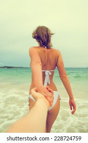 Woman holding man's hand and leads to the sea. Vintage effect.