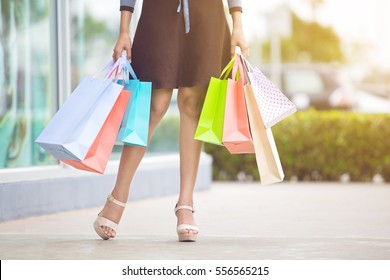 Woman holding many shopping bags in fashion boutique
