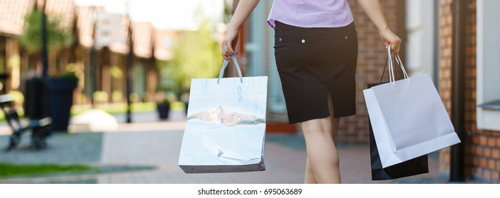 woman holding many shopping bags in fashion boutique, close-up, buttocks