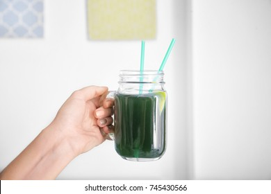 Woman holding mason jar with fresh spirulina drink on light background
