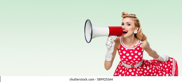 Woman holding megaphone, dressed in pin-up style dress, on green background. Caucasian blond model posing in retro fashion vintage studio shoot. Copyspace area for advertising slogan or text message.