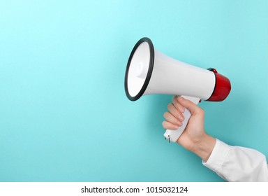 Woman holding megaphone on color background