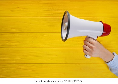 Woman holding megaphone on color wooden background