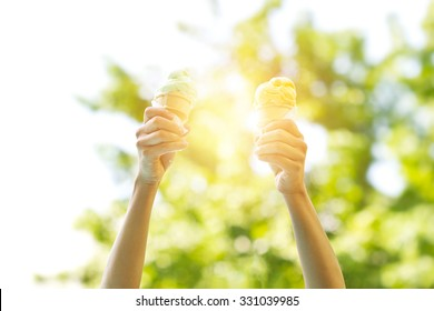 woman holding melting ice cream waffles cone in hands on summer light nature background