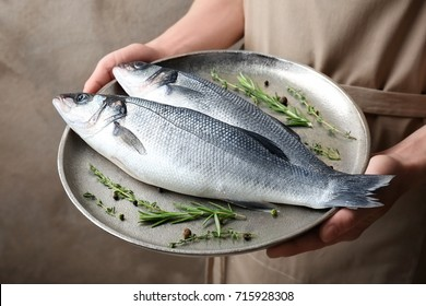 Woman holding metal dish with fresh fish in hands