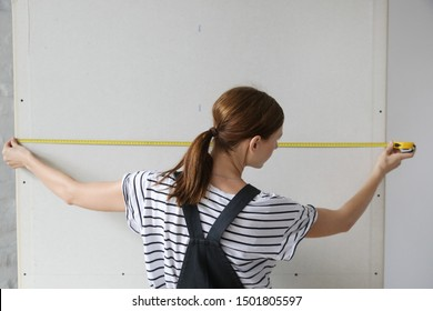 Woman holding a meter, measuring dimensions on plasterboard panel - DIY home improvement concept