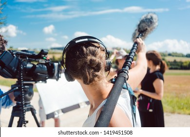 Woman holding microphone on a boom during video production capturing audio - Shutterstock ID 1419451508