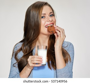 Woman holding milk glass bite cookie. Isolated female portrait with healthy food.