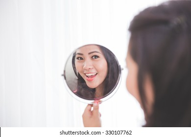 Woman holding a mirror, smiling brightly looking at her face