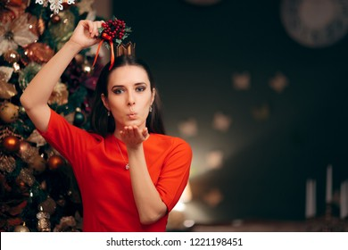 Woman Holding Mistletoe Ready for a Kiss. Girlfriend happy to share a kiss at Xmas party celebration
