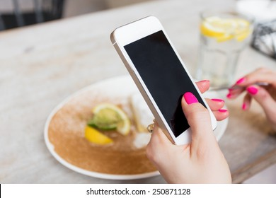 Woman holding mobile phone in cafe