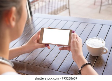 Woman holding mobile phone in horizontal position with isolated screen for mockup. Coffee cup and wooden desk in background.